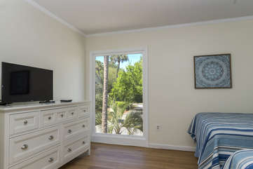 A large window fills this guest bedroom with light.  There is an HDTV in the room.