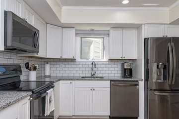 The renovated kitchen has bead board cupboards and stainless steel appliances.