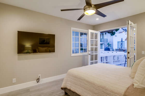 Ground floor, Queen bed room with flat screen TV,  french doors out to the deck, court side views.
