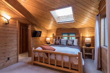 Master bedroom with King bed and flat screen TV on upper level