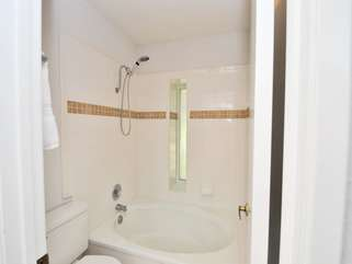Private tiled shower, tub with toilet area with door