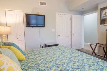 Master bedroom area with a king sized bed and flat screen TV for entertainment purposes