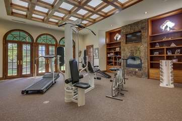 The full gym with free weights, exercise bike, bench, pull down nautilus machine and treadmill opens up to the pool area through 3 sets of french doors