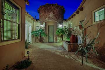 The front courtyard is gated with pavers and a custom fountain