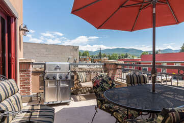Private patio with outdoor dining, gas grill, and premium views