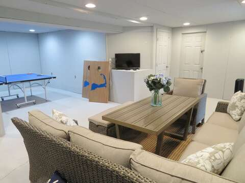 Lower level game room with ping pong and a seating area with a game table and flat screen TV - 162 Owl Pond Brewster Cape Cod - New England Vacation Rentals