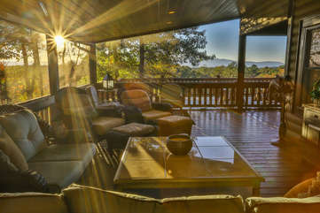THe screened side porch is spacious with plenty of seating.