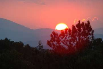 Peaceful view of the sun rising over a mountain in the early morning.