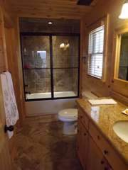 The bedroom on the Main Level of the cabin offers a Tile Tub Shower unit with private access from the bedroom on the main.