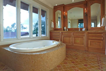 Bathe in style in the soaking tub or walk-in rain shower of the main bedroom's en suite bath