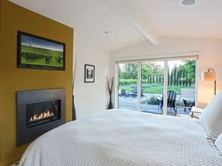 Main bedroom with all the extras — fireplace, TV, deluxe bedding, and remote-controlled window shades!