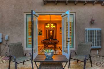 The pool table area has French doors that open up to a separate seating area on the side of the home
