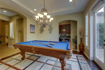 The pool table area has a bar nook with refrigerator and French doors leading to the outside