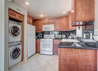 Open kitchen with stacked laundry tucked away!