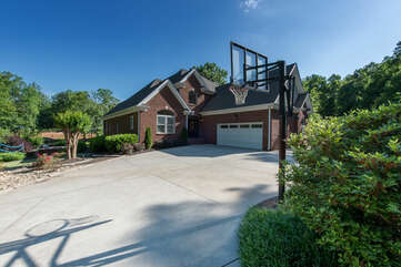 Driveway with plenty of space, 2 car garage and basketball hoop.