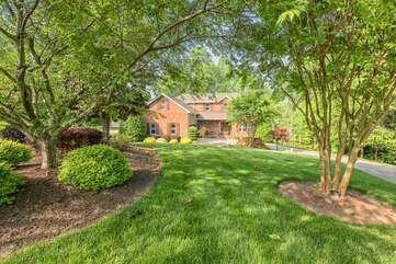 Mature trees, lush green grass add to this beautiful home.