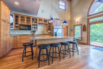 Large island for all to gather in kitchen, off living room. Bar stool seating for 6.