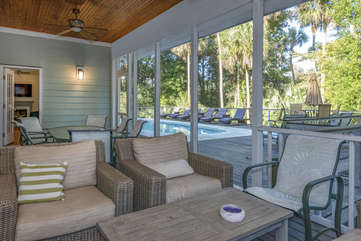 Conversation seating on screened porch accessible from living room, master bedroom, kitchen and pool deck