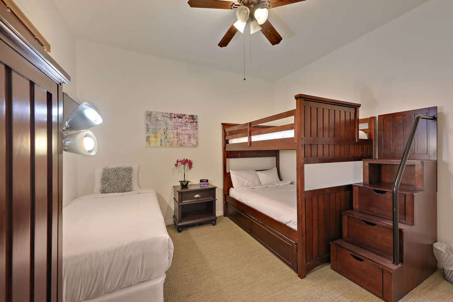 Guest bedroom with bunk bed (full on top and bottom) plus additional twin bed.