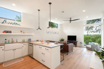 This NEW Mediterranean cottage is beautifully appointed with hand scraped hardwood flooring, quartz countertops, high-end furnishings, and floor to ceiling windows.
