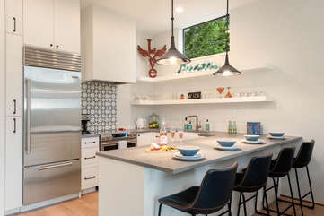 The fully equipped kitchen features a custom plaster vent hood, stainless steel appliances - and everything you need for enjoying meals at home.