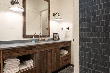 The main bathroom features custom tile and designer fixtures.