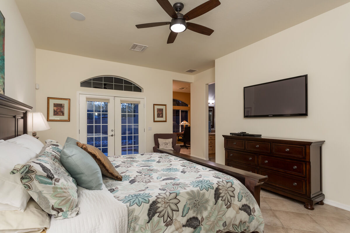 Master Suite has a King Sized Bed, Wall Mounted HD Smart TV,  Attached Office, Attached Master Bath & French Doors Leading to Patio Area.