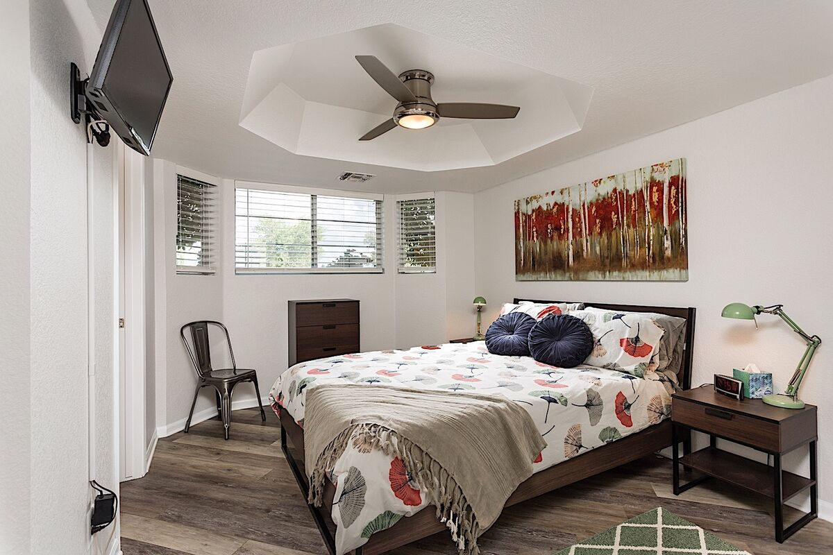 A vaulted ceiling and warm colored accents make this bedroom a calming retreat