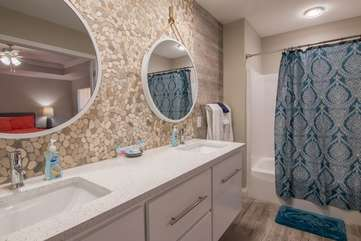 Beautiful bathroom complimented with a stone wall backdrop connected to dual sinks is attached to the master bedroom on 2nd floor