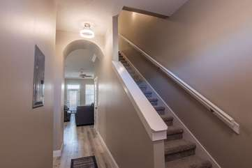 Perspective of the house as you enter it with the stairs to your right leading upwards to the other 3 bedrooms, guest bathroom, and laundry room and your hallway that leads into the living/ kitchen area