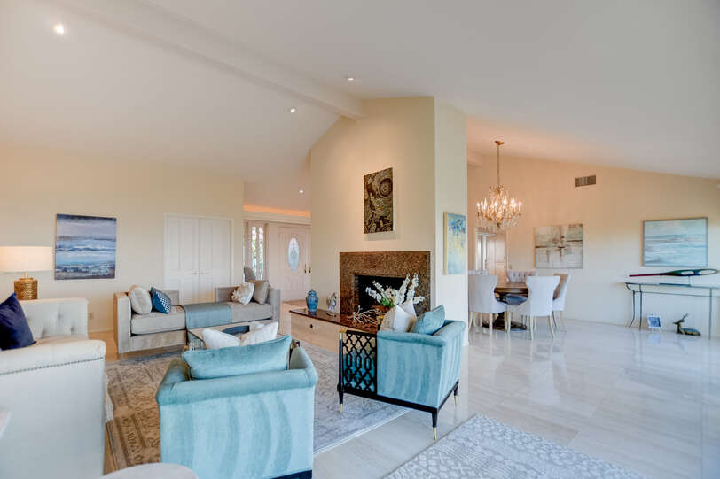 The formal living area features a stately fireplace and comfortable seating