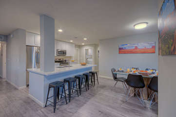Kitchen with bar seating transitions into a spacious dining area for formal or informal meals