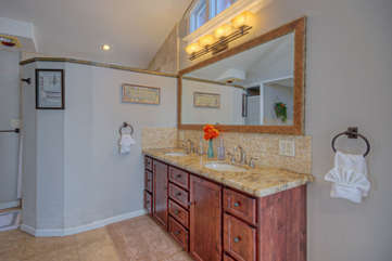 The bath in master suite has a large vanity with dual sinks and a granite top
