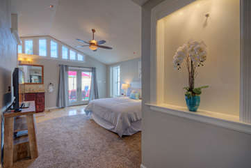 Bright with natural light the master suite features a vaulted ceiling and doors to the backyard oasis