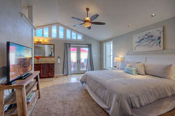 Master suite with vaulted ceiling features a king bed and large television