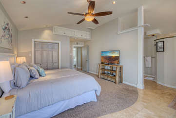 The master suite has a large television and ceiling fan
