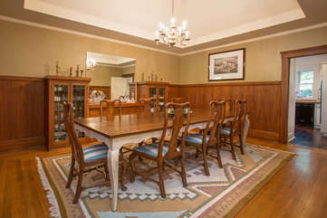 Spacious dining room has a high ceiling, wood paneling, and table for 8+