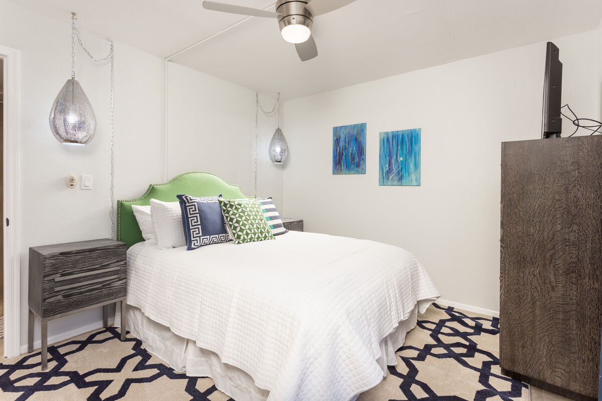 Master bedroom has a queen sized bed, flat screen TV and patio entrance