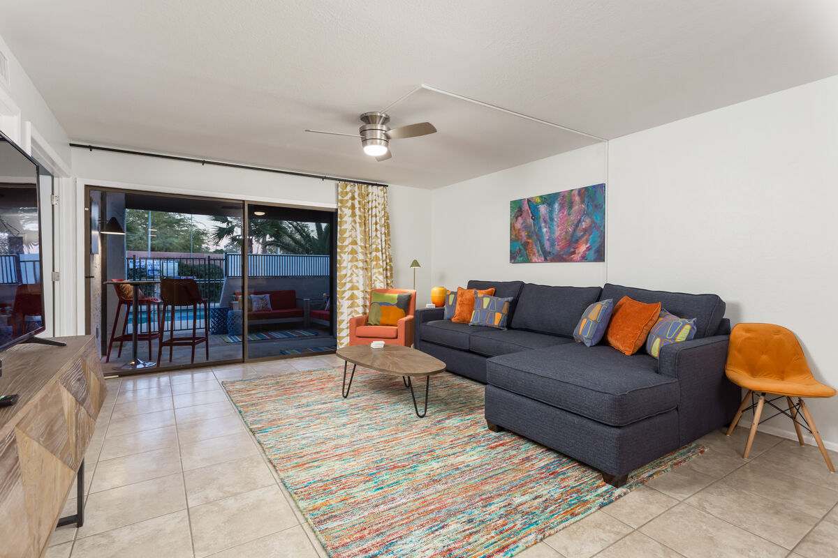 Living room has a large sectional sofa and a flat screen HD TV. Patio opens to lounge area and pool entrance.
