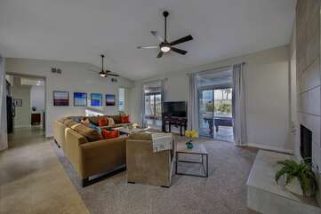 Living room has 2 modern ceiling fans for air circulation and TWO sliding glass doors leading out back
