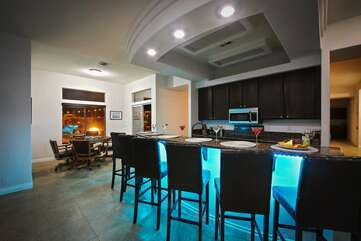 The kitchen center island doubles as a huge functional bar area with barstools and sink for your occasion