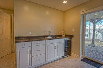 wet bar downstairs with drink refrigerator