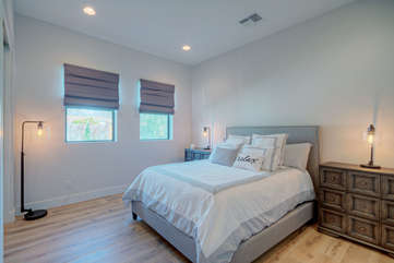 Second bedroom with ensuite bath has a cozy queen bed, and vaulted ceiling