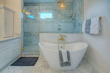Ensuite bath in primary bedroom includes a sumptuous tub for soaking away your stress