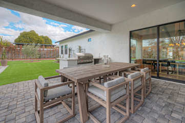 Celebrate the good life with your favorite peeps under the large covered porch in lush backyard