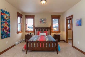 Colorful queen bedroom (upstairs) with ensuite bathroom, closets & large deck w/ seating