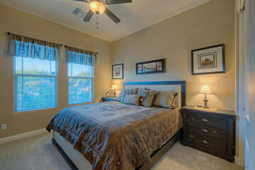 The fourth bedroom features a king bed, windows with a view and ceiling fan