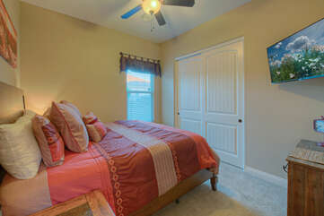 The fourth bedroom also has a king bed, ceiling fan and television