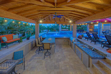 The backyard oasis includes a pool bar, large grill, fridge/freezer, dishwasher and cozy furniture for relaxing and dining poolside