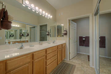 Lighting and dual vanity sinks in the primary suite bath facilitate primping for an evening on the town